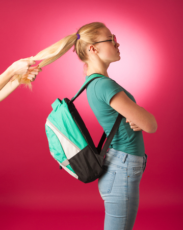 resisting: Stubborn, angry schoolgirl resisting to go to school. Wearing backpack and big eyeglasses, someone pulling her for two hair tails.