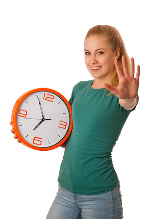 Blonde woman holding big clock in hand, gesturing five minute to seven oclock, isolated over white.