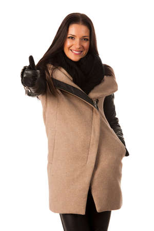 successes: Woman in winter coat standing confidently showing thumb up and smiling. Business woman prepared for winter successes. Stock Photo