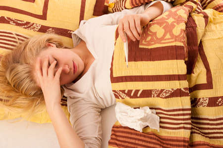 Sick woman lying in bed covered with blanket, feeling ill, has flu and fever. She has inflammation of the sinuses and headache.