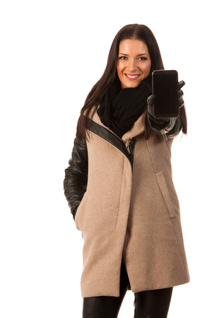 successes: Woman in winter coat standing confidently, showing screen of cell phone and smiling. Business woman prepared for winter successes. Stock Photo