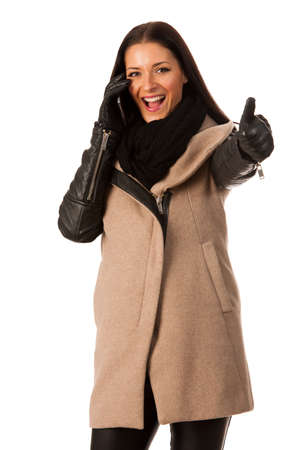 successes: Woman in winter coat standing confidently with thumb up talking over cellphone and smiling. Business woman prepared for winter successes.