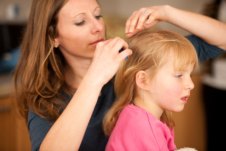 Mother combs hair to a cute little girl