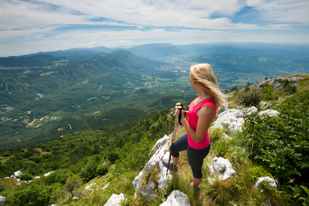 Trekking - woman hiking in mountains on a calm sumer day