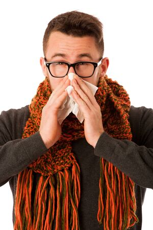 Man with flu and fever wrapped in scarf sneezing into handkerchief isolated over white.