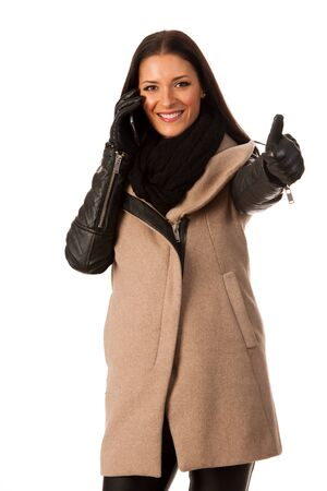 Woman in winter coat standing confidently with thumb up talking over cellphone and smiling. Business woman prepared for winter successes.