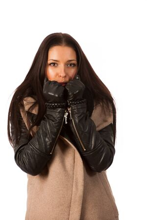 successes: Woman in winter coat and gloves, trying to heat hands with blowing in them. Business woman prepared for winter successes.