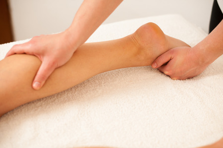 Therapist massaging a leg in a wellness center  - spa
