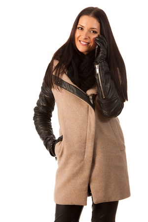 successes: Woman in winter coat and gloves, standing confidently, talking over phone and smiling. Business woman prepared for winter successes.