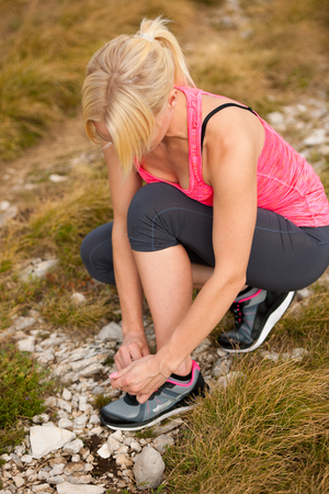 woman tie: sporty woman tie shoe ona a path outdoor before running