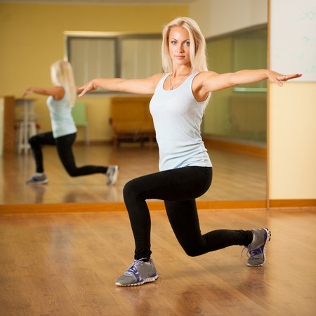 Frau fit trainieren im Fitness-Studio Longe Schritt machen