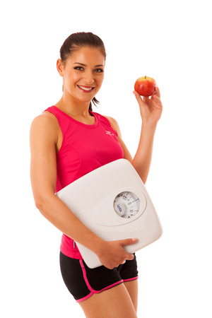 Woman holding scale and apple for healthy lifestyle and nutrition