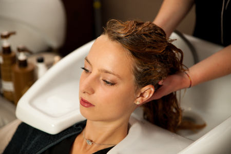 shampooing: Hair stylist at work - hairdresser washing hair to the customer before doing hairstyle Stock Photo