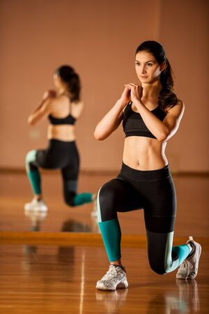 Beautiful fit woman works out in a fitness gym making lunge steps  for leg strength