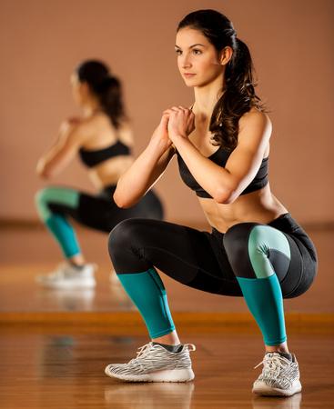 Bella donna di misura facendo squat in palestra Archivio Fotografico - 69354348