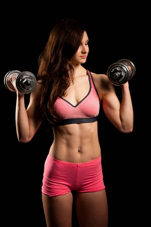 atractive: Atractive fit woman works out with dumbbells as a fitness conceptual over dark background. Stock Photo