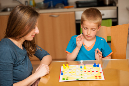 ludo: young boy plays ludo game with his mother on a table in livingroom