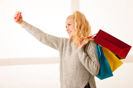 Beautiful blonde woman taking selfie with smart phone after shopping in mall. Stock Photo