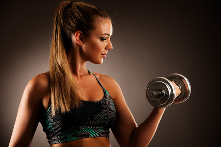 fit woman workout with dumbbells in gym studio photography of a bikini fitness competitor Stock Photo