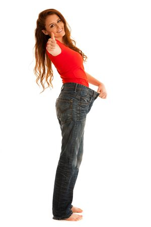 uvolněný: Beautiful young woman holding scale and too big trousers as she lost weight