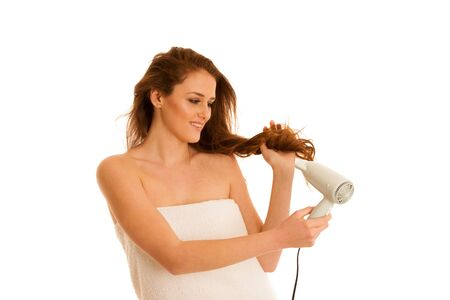 blow dryer: beautiful young woman dries hair  with a blow dryer