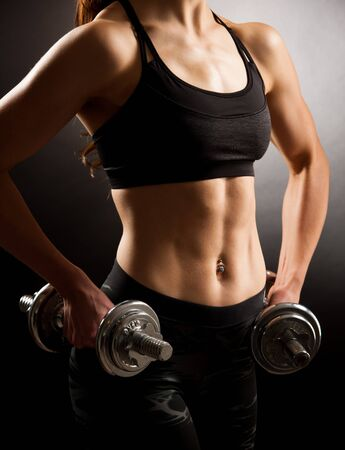 Atractive fit woman works out with dumbbells as a fitness conceptual over dark background. Stock Photo