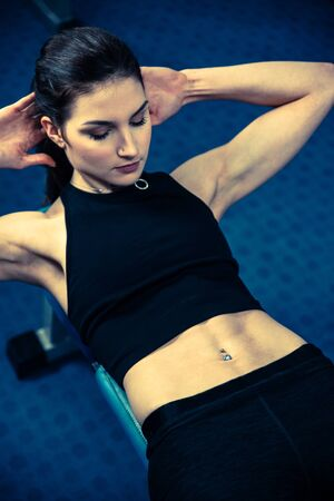 Attractive fit woamn working out abs in fitness gym, making ab intervals