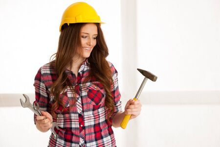 power wrench: Woman holding a hammer and wrench on a workshop
