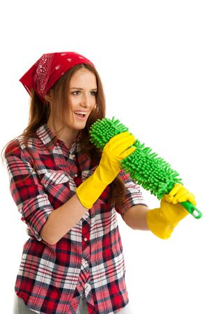 Beautiful young woman cleaning dust in checkered shirt isolated over white background. Stock Photo