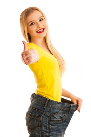Woman gesturing success as she lost weight wearing too big trousers isolated over white Stock Photo