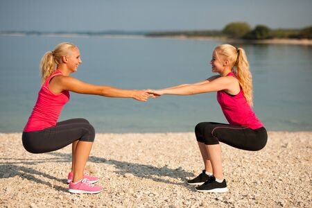 Two women exercise on beach doing squats
