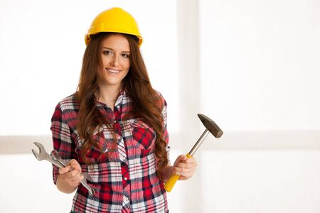 Woman holding a hammer and wrench on a workshop