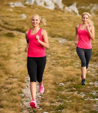 runner - woman runs cros country on a path in early autumn Stock Photo