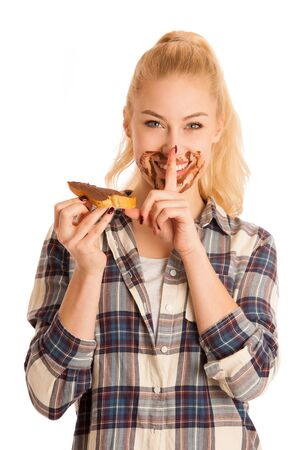 Young blond woman eating breakfast bread and nougat spread isolated over white background.