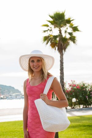 stilish: young stilish woman in pink short summer dress walks around a costal city on her vacations