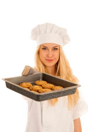 beautiful blond woman in chef dress bakes cookies isolated over white background