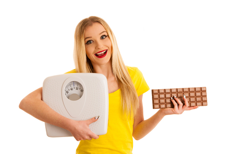 Undecided woman holding scale and chocolate uncertain wether to loose weight isolated over white background