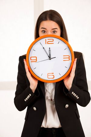 cute woman holding a clock as a symbol of time management