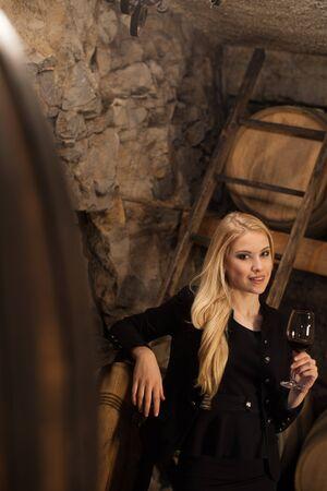 degustation: Beautiful young blond woman drinks wine in wine cellar