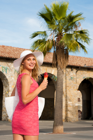 Beautiful young woman with ice cream in a costal city on a hot summer day