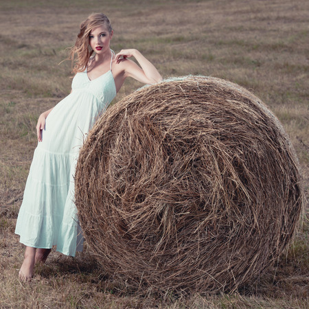 attractive stylish Woman in  long white summe dress near hay bale on meadow