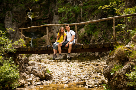knelt: active young cople hiking on a wooden brifge over mountain creek Stock Photo