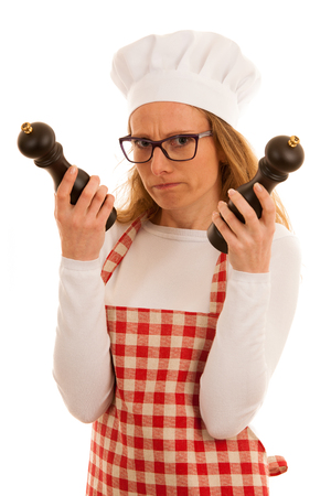 Uncertain chef with salt and pepper grinder isolated over white Stock Photo