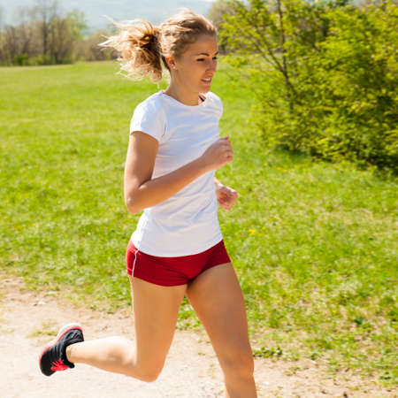Woman runner runs - workout in spring.