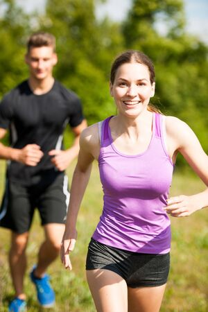 active young youple running in nature on a fores path Stock Photo