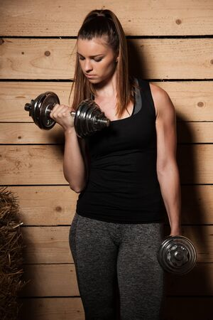 Active young woman work out with dumbbells in fitness gym Stock Photo