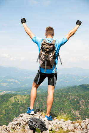 Aczive young amn gesture success after climbing a mountain