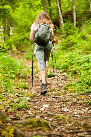 Active hiker hking on a narrow path in forest on a early spring afternoon