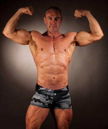 bodybuilder pose in studio over dark background