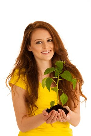Beautiful young woman holds seedling isolated over white background